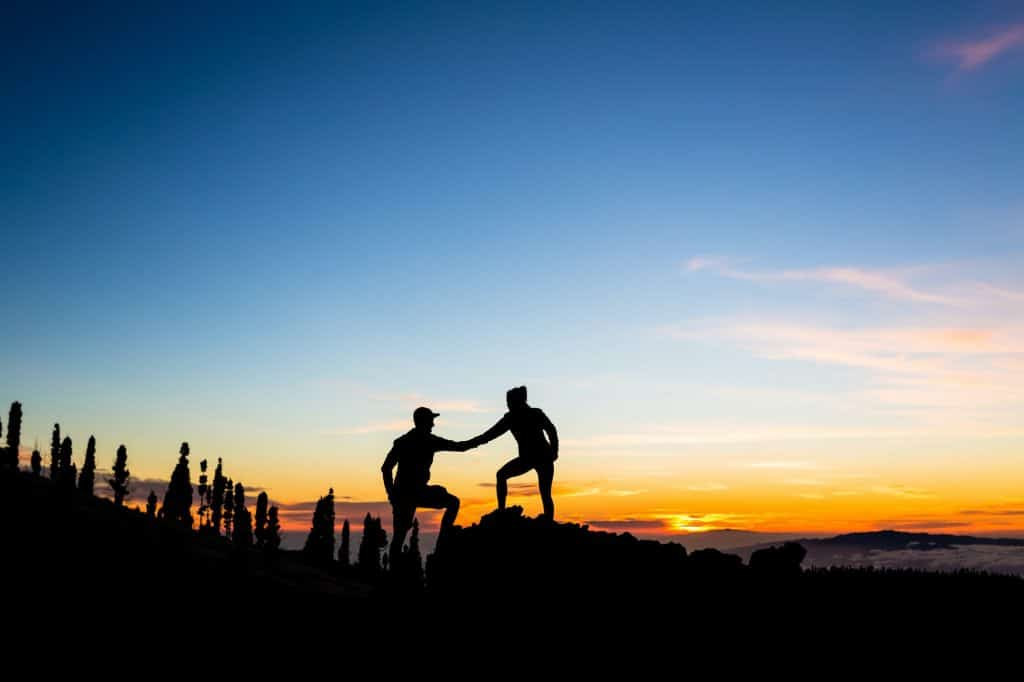 Teamwork couple climbing with helping hand