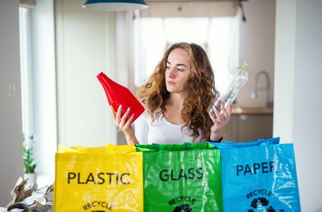 Young woman indoors at home separating glass, paper, and plastic waste